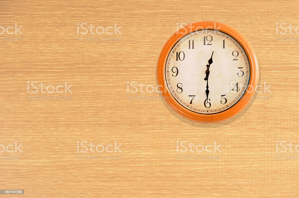 Clock showing 12:30 o'clock on a wooden wall stock photo