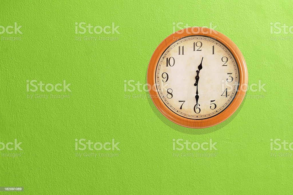 Clock showing 12:30 on a green wall stock photo