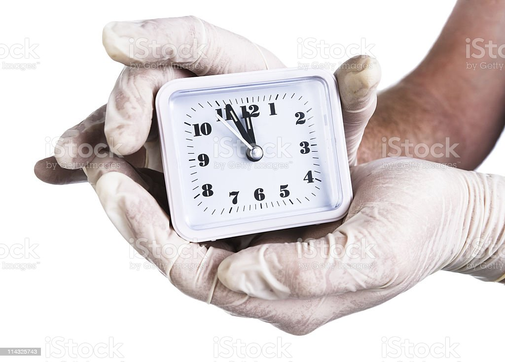 Clock  showing 23h59 clasped in gloved hands stock photo