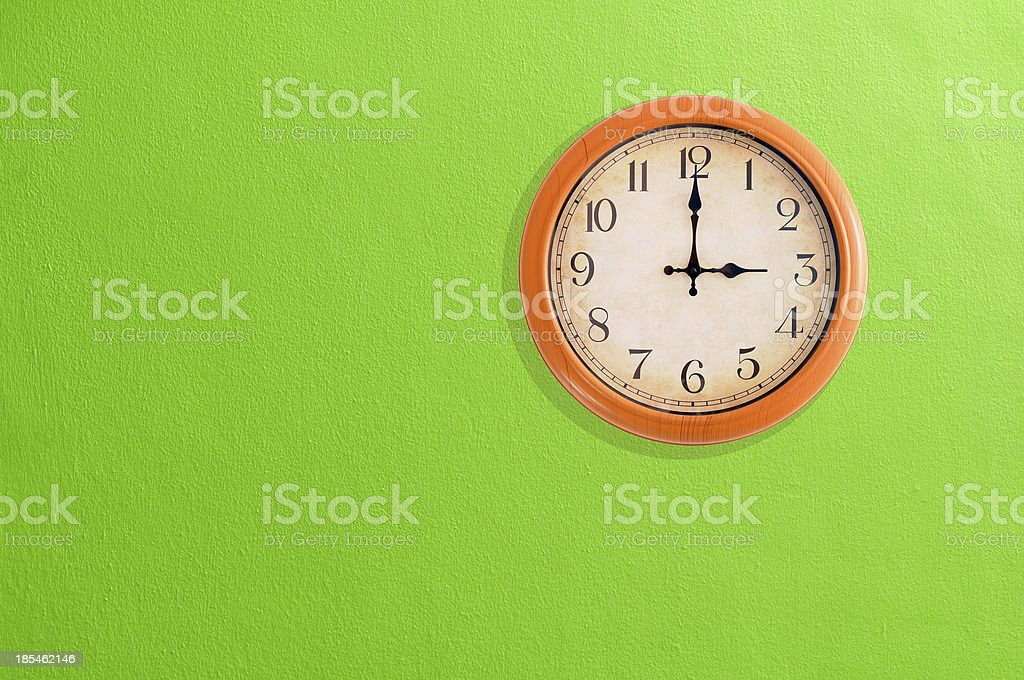 Clock showing 3 o'clock on a green wall stock photo