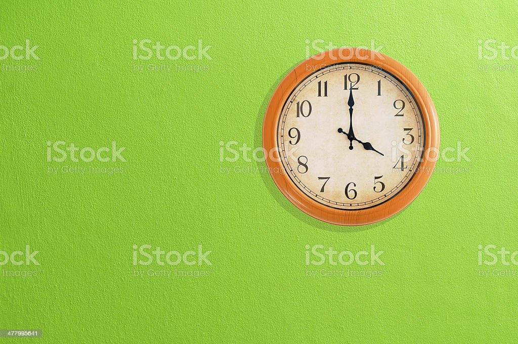 Clock showing 4 o'clock on a green wall royalty-free stock photo