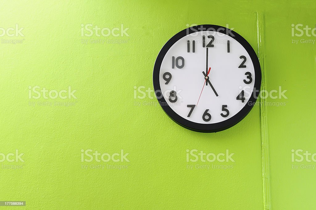 Clock showing 5 o'clock on a green wall stock photo