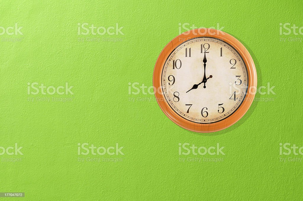Clock showing 8:00 on a green wall royalty-free stock photo
