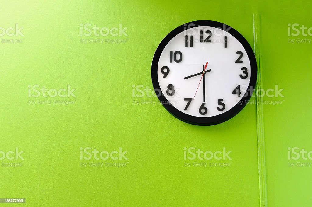 Clock showing 8:30 o'clock on a green wall stock photo