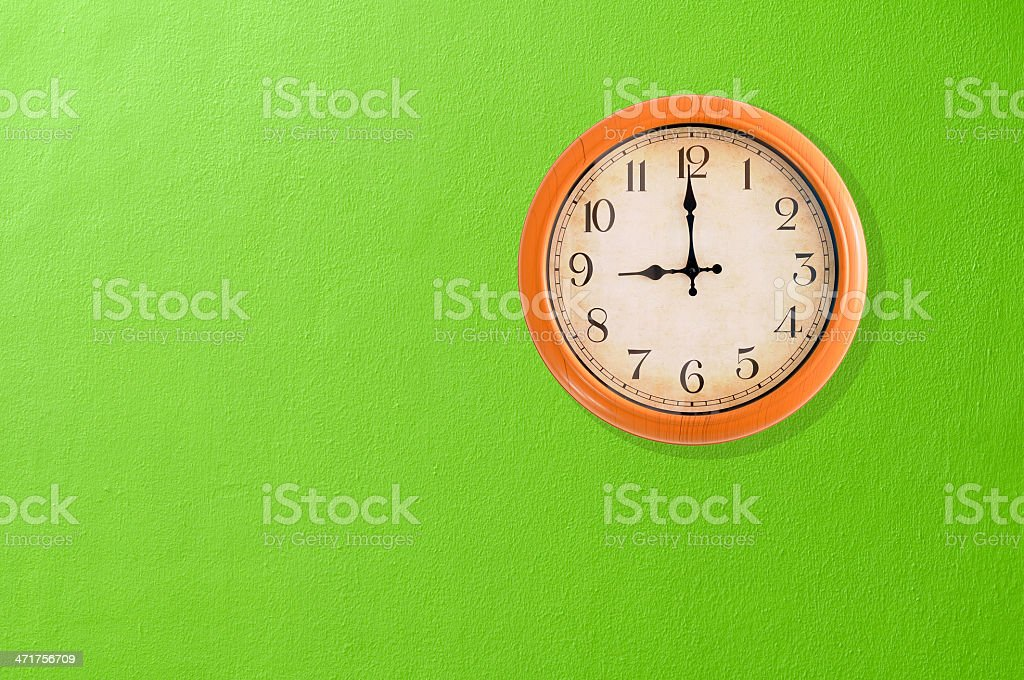Clock showing 9 o'clock on a green wall royalty-free stock photo
