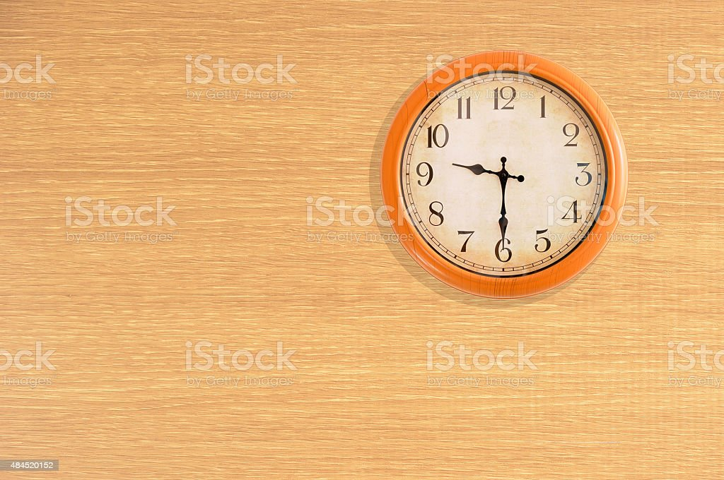 Clock showing 9:30 o'clock on a wooden wall stock photo