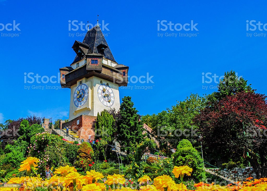 clock tower and beautiful flowers in garden, Graz, Austria stock photo