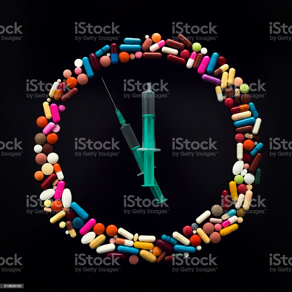 clock with colorful pills and syringe on black background stock photo