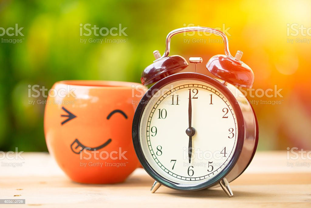clock with smile coffee cup, wake up morning concept. stock photo