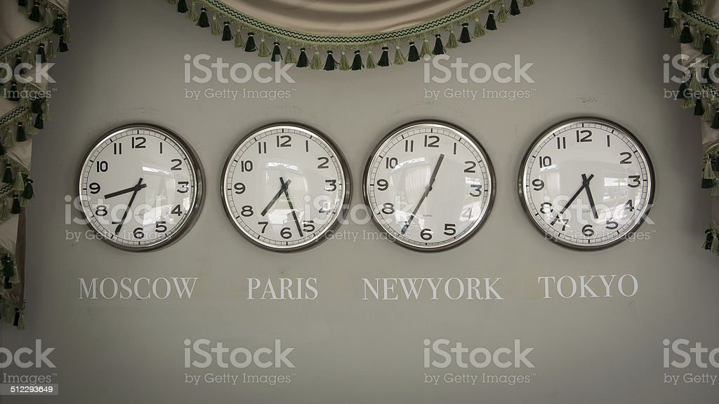 clocks on a wall with time zone of different country stock photo