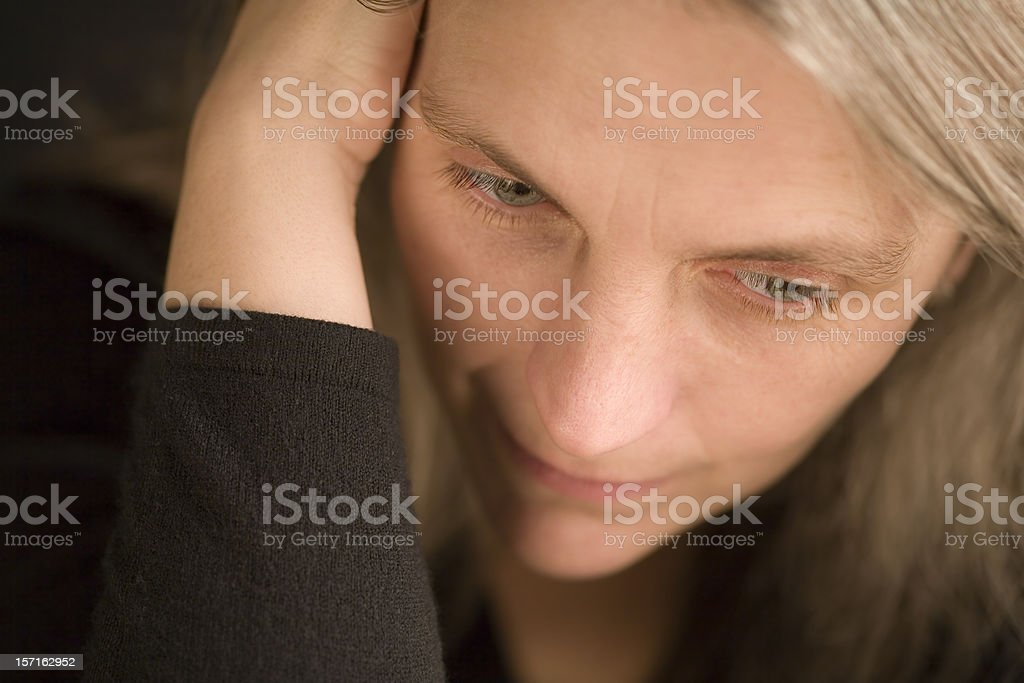 Close, candid detail on a mature woman holding her head stock photo