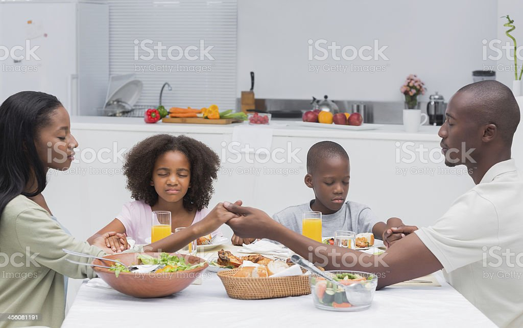 Close family saying grace before having dinner stock photo