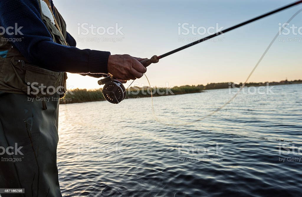 Close of Fly Fisherman's Reel and Hands stock photo