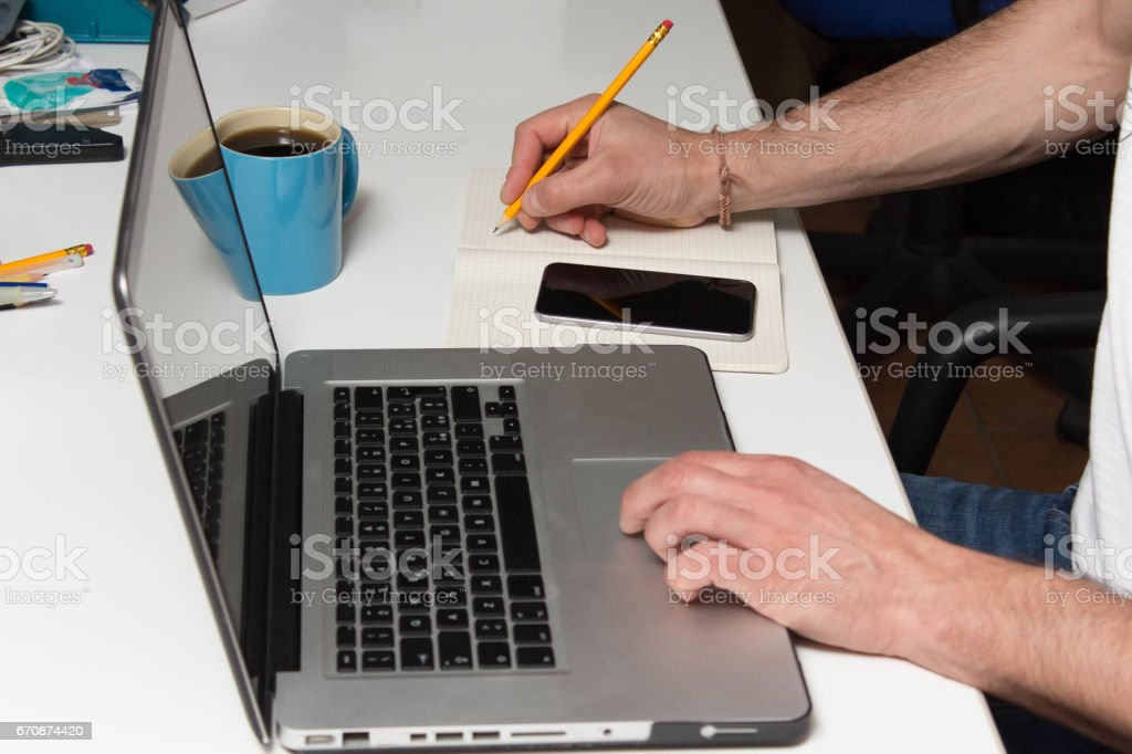 Close photo man hands using laptop on desk stock photo