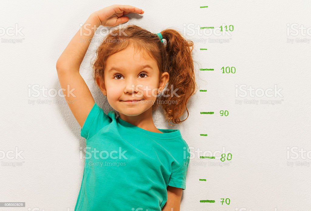 Close portrait of a girl show height on wall scale stock photo