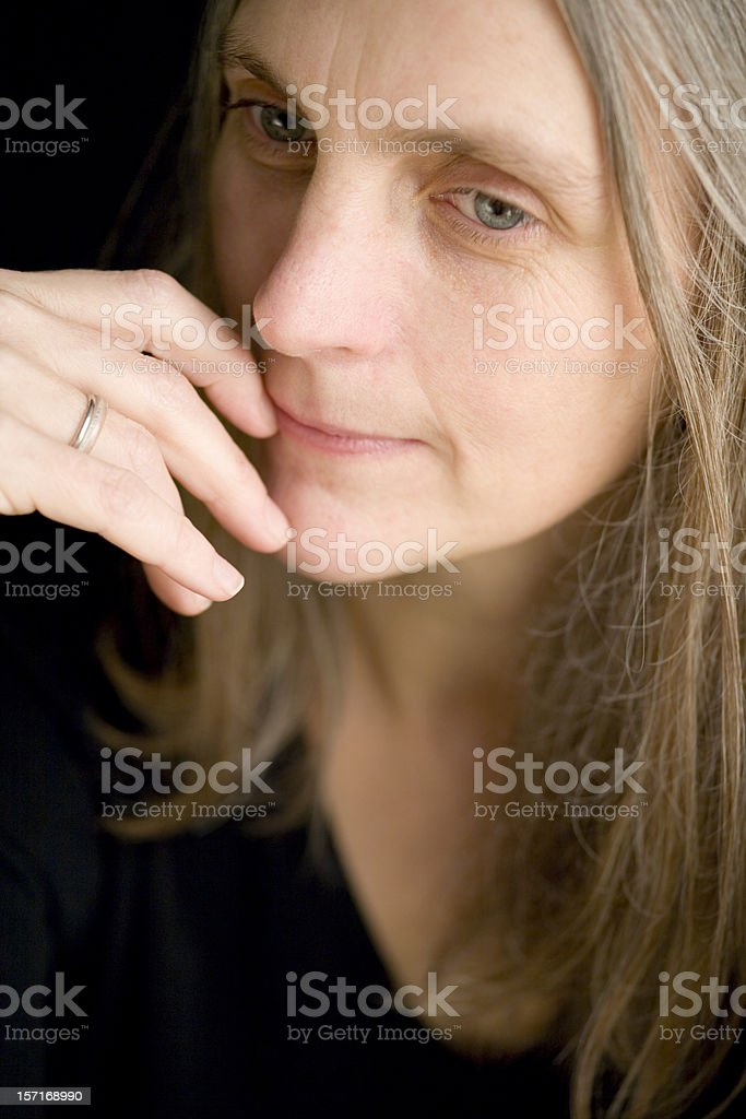 Close portrait of a mature woman in a pensive mood royalty-free stock photo