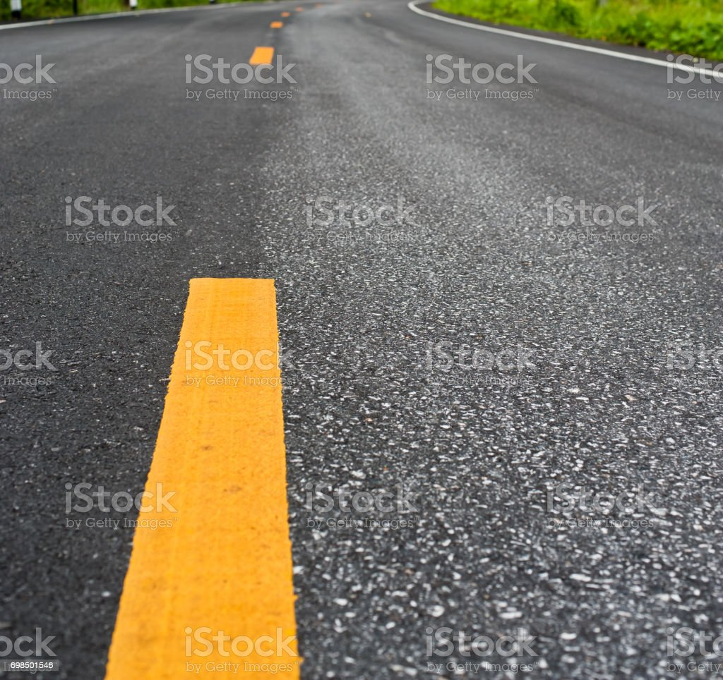 Close up asphalt surface of road divide yellow lines stock photo