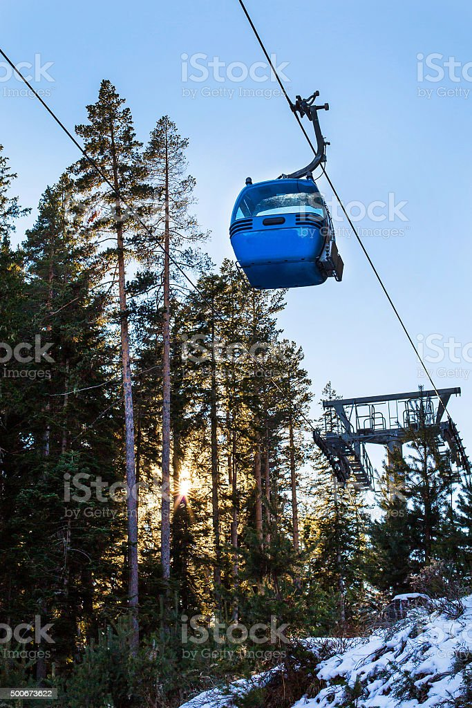 Close up Bansko cable car cabin, pine trees and sun stock photo
