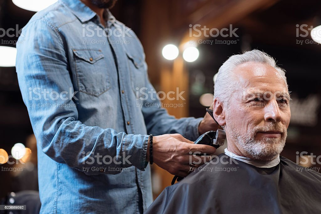 Close up barber trimming hair of old man stock photo