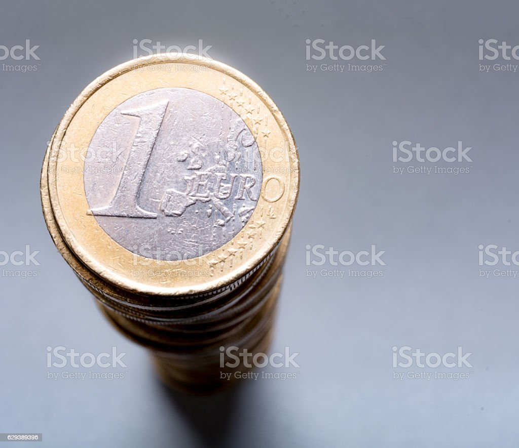 Close up Battered but shiny euro coin on large stack stock photo