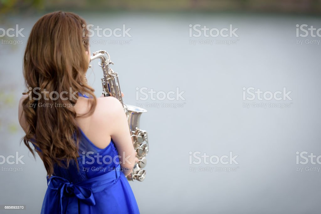 Close up Beautiful woman wear blue evening dress sound saxophone over mountains and rivers background. stock photo