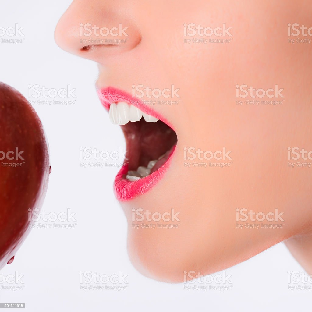 close up beautiful young woman mouth biting a red apple stock photo