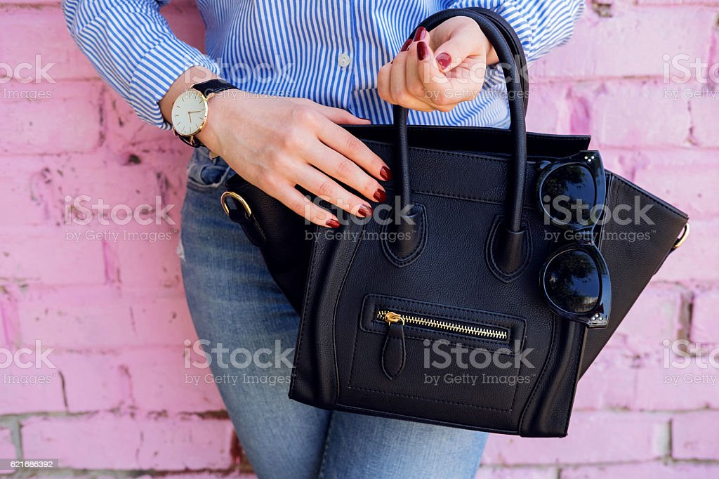 Close up black leather bag in hand of fashion woman. stock photo