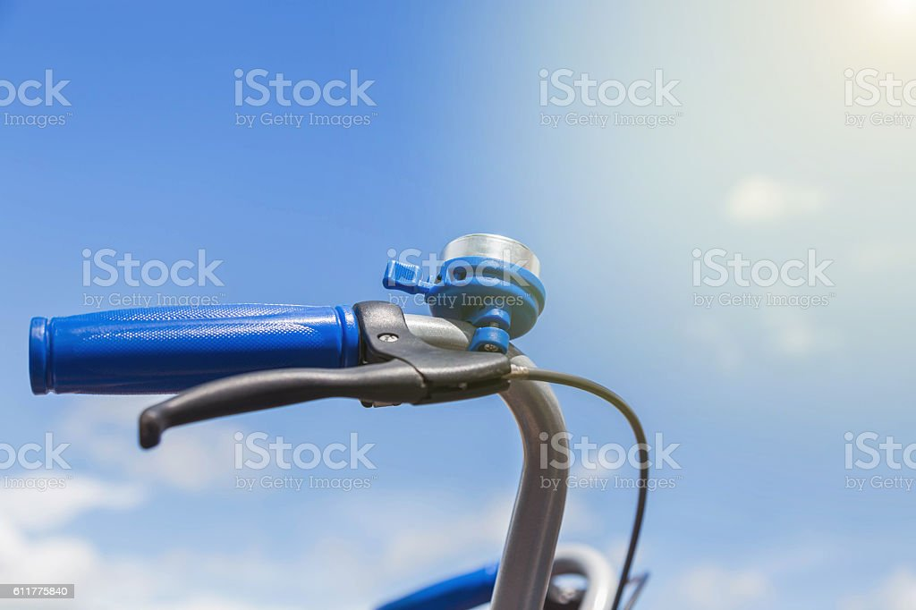 close up blue bicycle bell with blue grip on handle bar stock photo