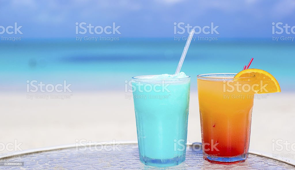 Close up Blue Curacao and Mango cocktail on white beach stock photo