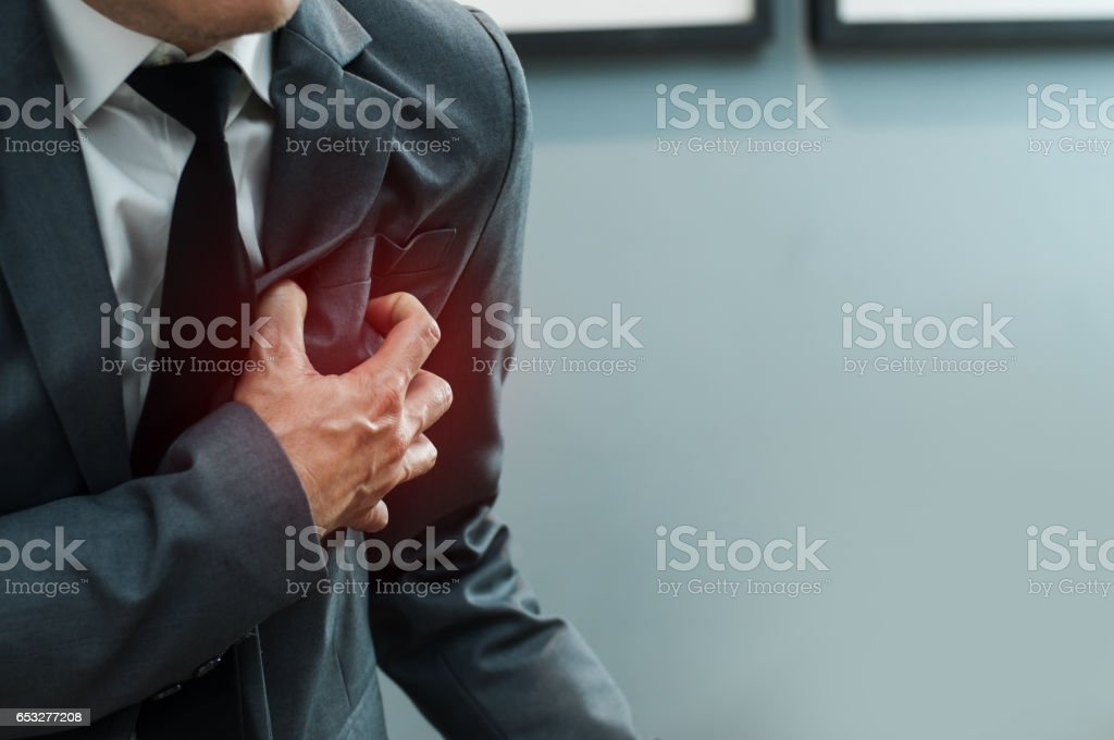 Close up Businessman in grey suit has heart attack. Exhausted, Illness, disease, tired concepts. stock photo