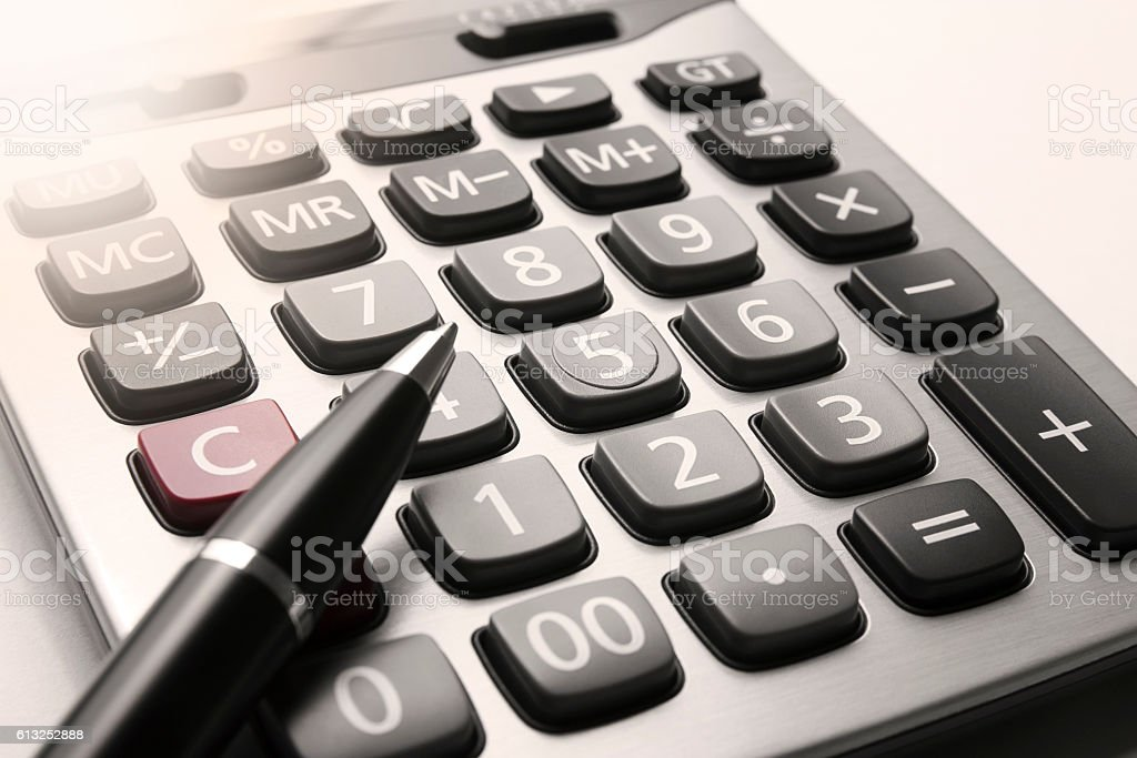 close up calculator with pen and flare stock photo