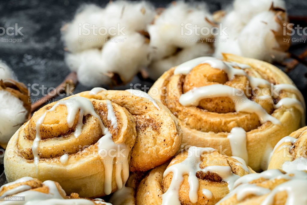 close up cinnamon rolls on the plate, on a dark cement table, cotton boxes behind. stock photo