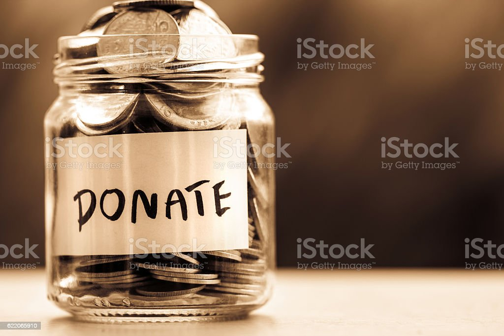 Close up Coins in glass jar for giving and donation stock photo