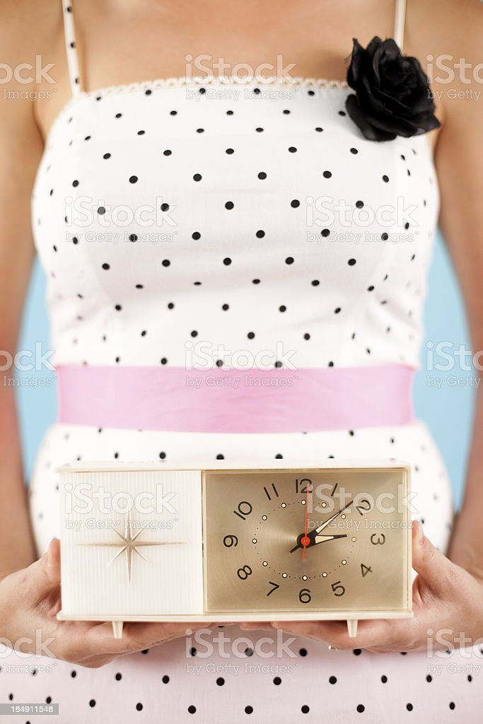 Close Up Color Image of Retro Gal Holding a Clock stock photo