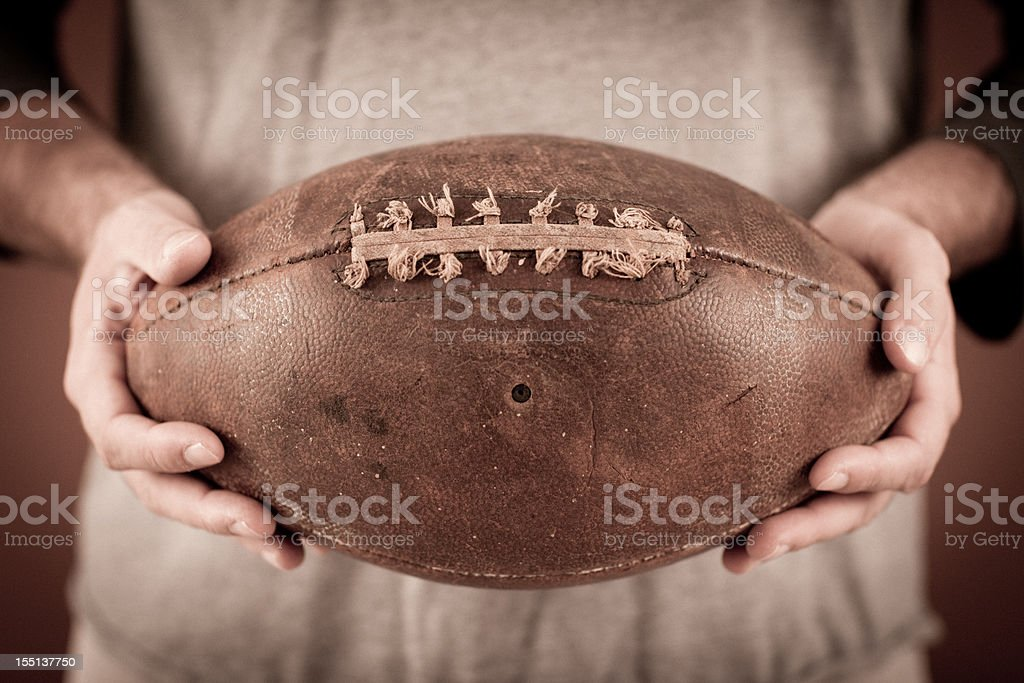Close Up Color Photo of Vintage Football Player Holding Ball royalty-free stock photo