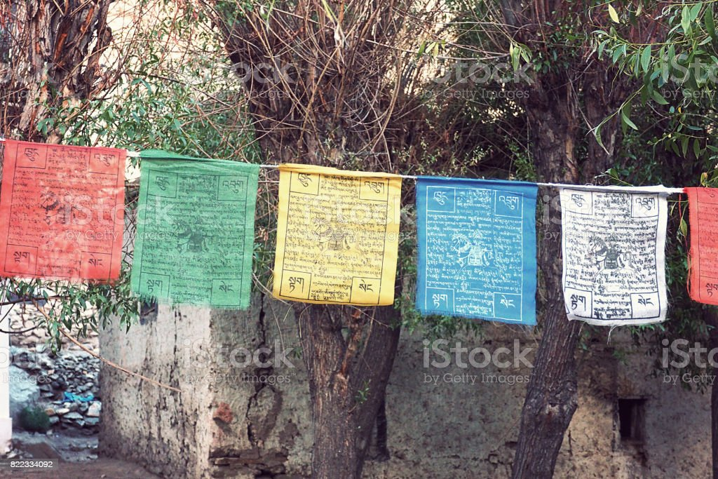 close up Colorful buddhism flags hanging in a tree stock photo