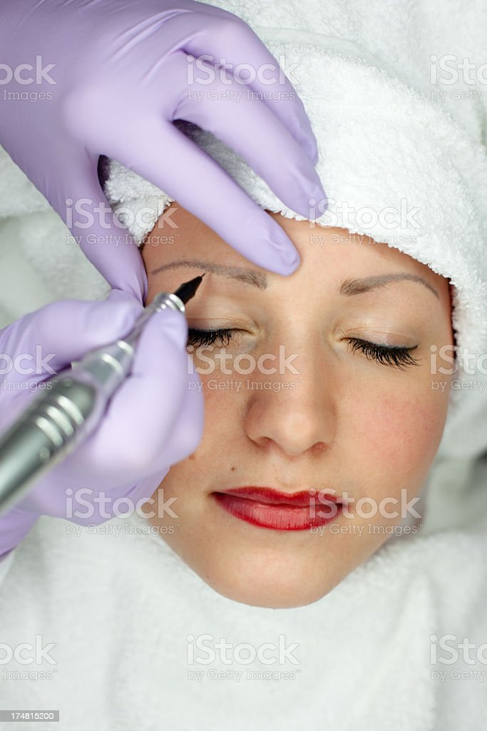 close up: cosmetician makes a permanent makeup on eyebrow royalty-free stock photo