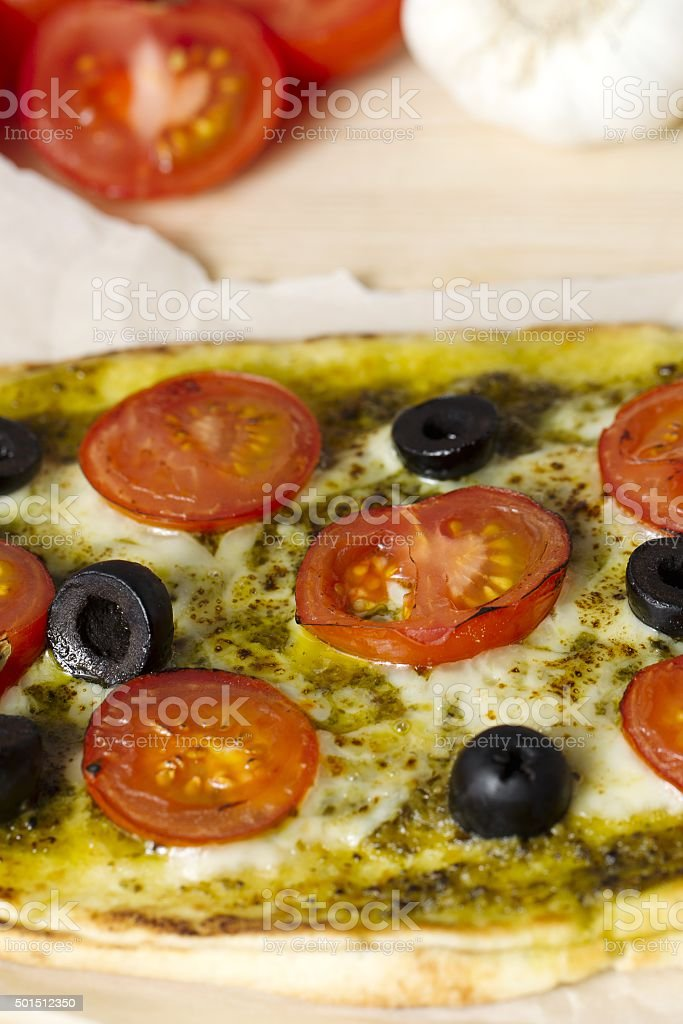 close up cropped shot of a pizza with vegetables toppings stock photo