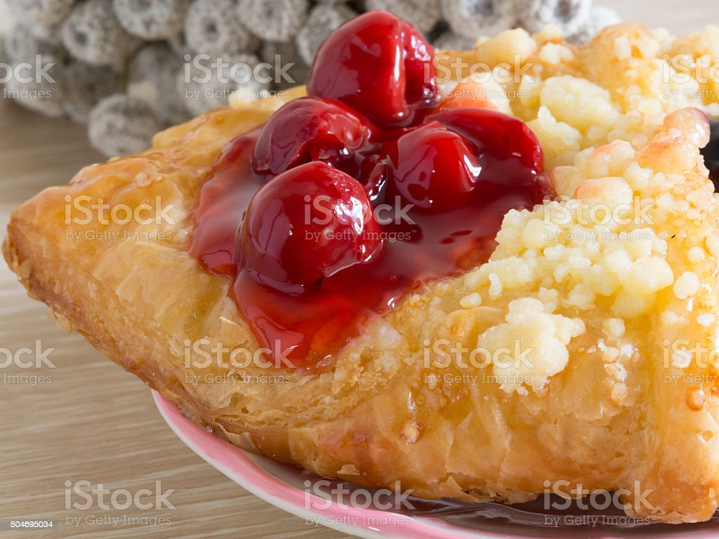 close up danish pastry with fruit on wood table stock photo
