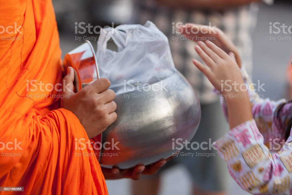 Close up detail of a Thai Buddhist Monk receiving alms from a young layperson, who has just put food into the monks alms bowl outside a Thai Buddhist temple in Bangkok. stock photo