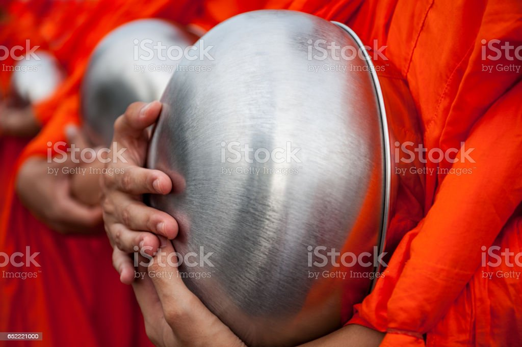 Close up detail of Thai Buddhist Monks holding alms bowls outside a Thai Buddhist temple in Bangkok. stock photo