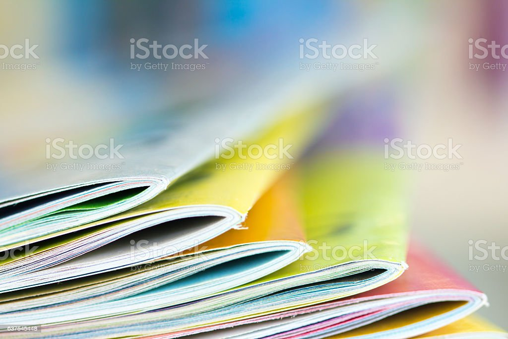Close up edge of colorful magazine stacking stock photo