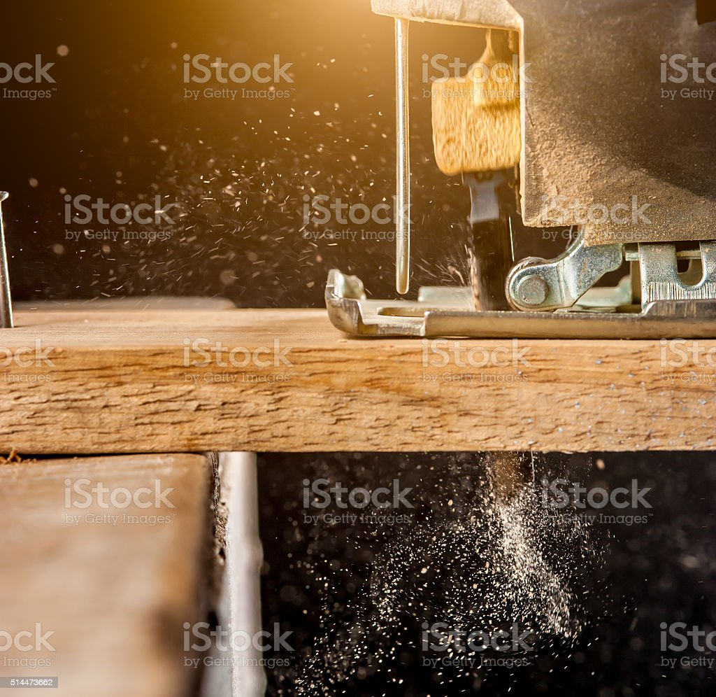 Close up electric jigsaw cutting a piece of wood stock photo
