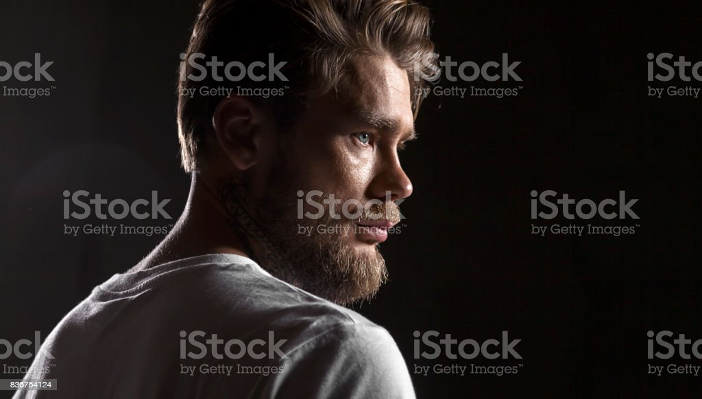 Close up face bearded man in white t-shirt on black background