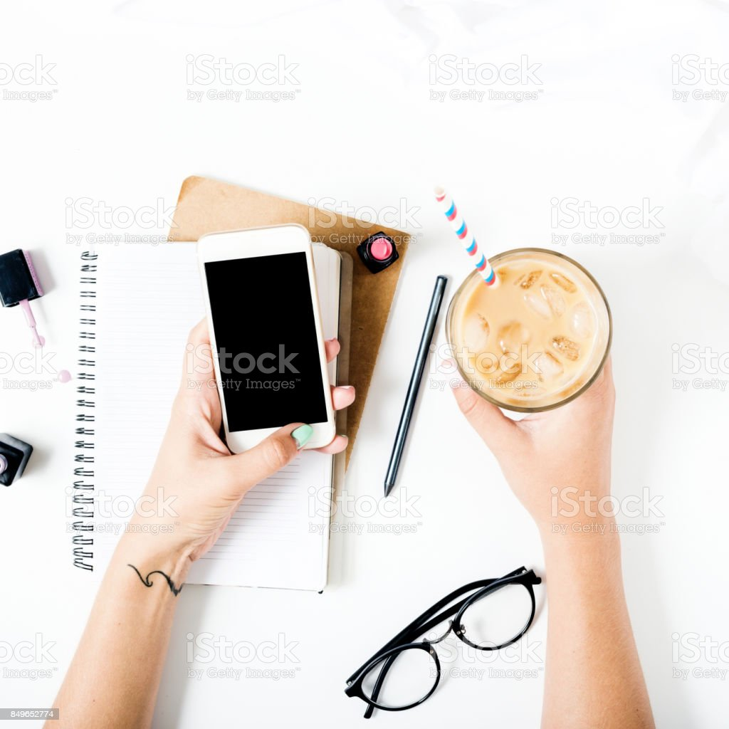 Close up feminine workspace with smartphone in female hands, latte ice, notebook, spectacles, nail polish and lipstick. Flat lay stock photo