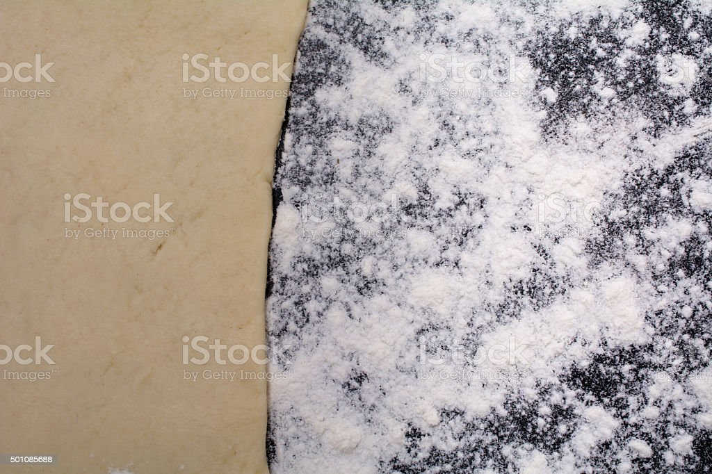 close up flour on black counter rolled out dough stock photo