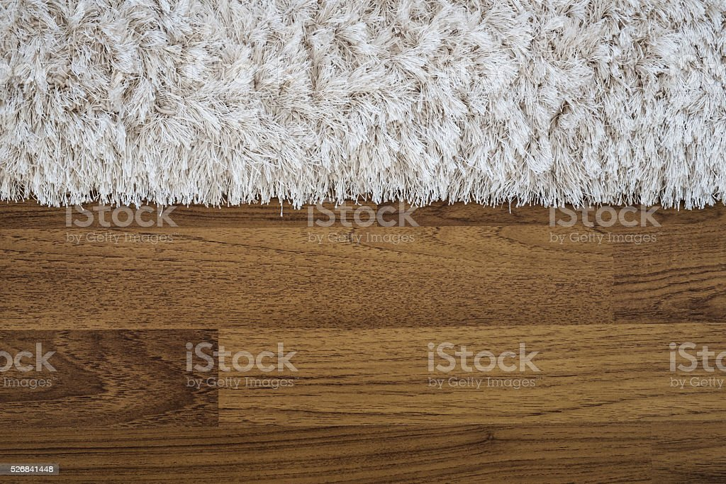 Close up fluffy luxury carpet on laminate wood floor stock photo