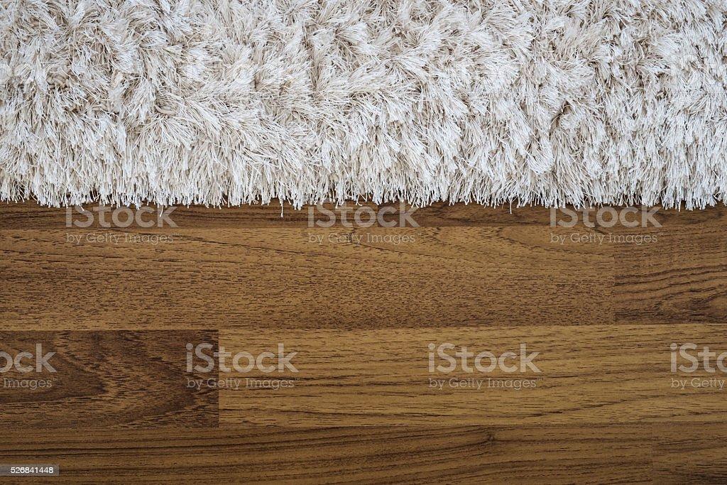 Close up fluffy luxury carpet on laminate wood floor stock photo
