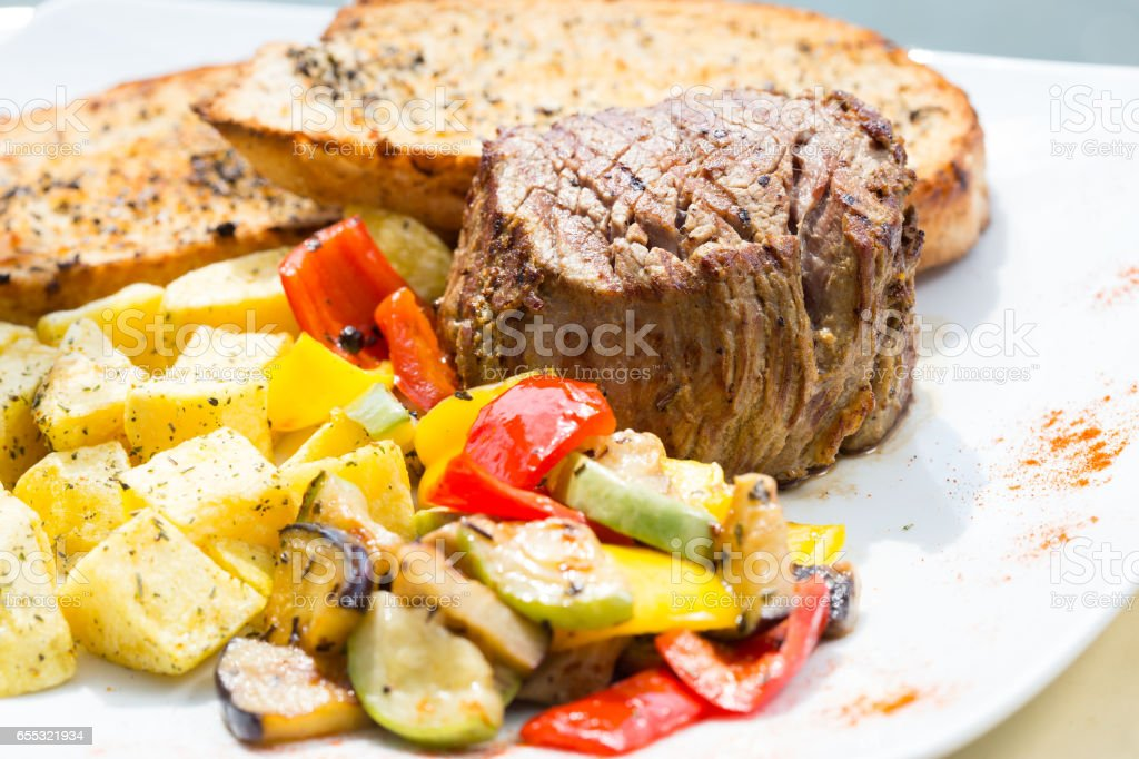 Close up Gourmet Appetizing Roasted Beef Steak with Potato Wedges and Other Vegetables on a Cast Iron Skillet stock photo