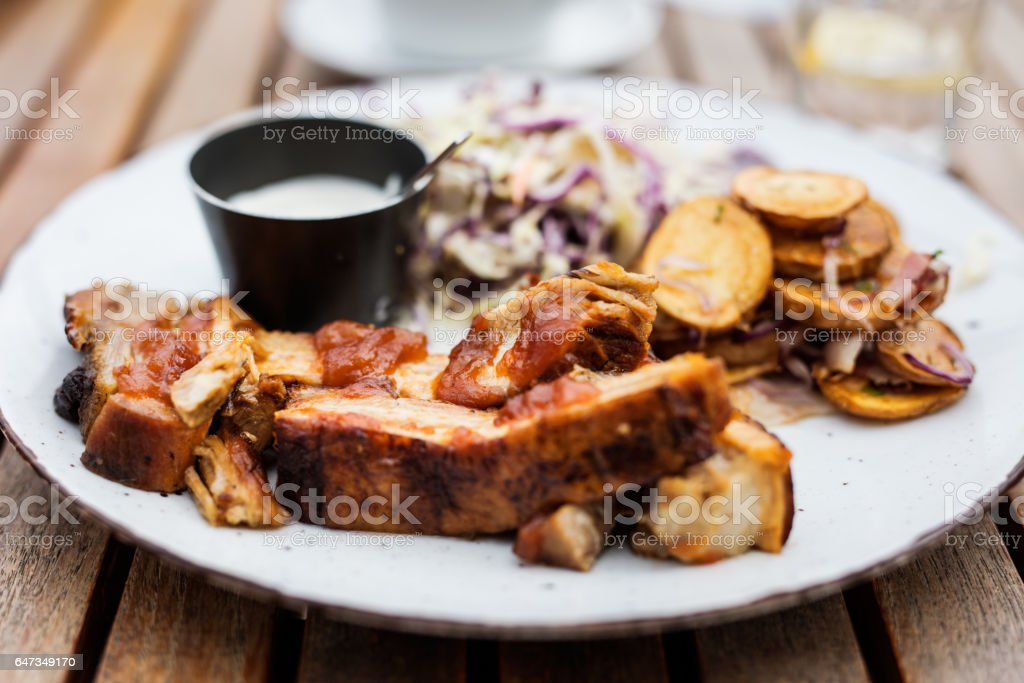 Close up Gourmet Grilled Pork Rib and Fried Potato Wedges on White Plate with Sauce and Veggies stock photo